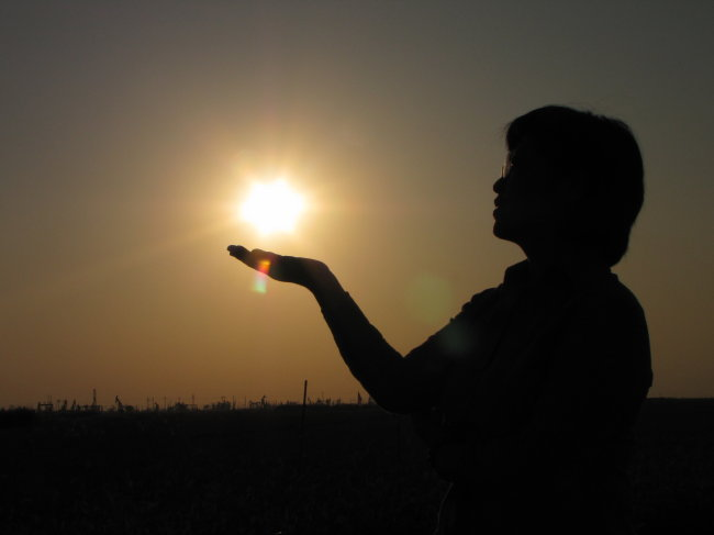 夕阳下手托太阳人物剪影